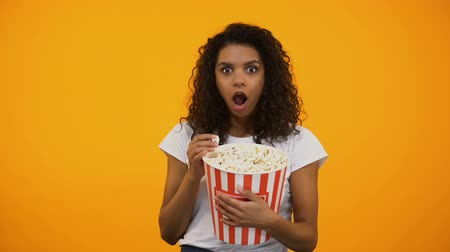 blockbuster : Excited African-American woman eating popcorn and watching interesting movie