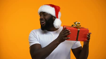 рождество : Afro-American man in Santa hat holding Christmas gift and winking, holiday