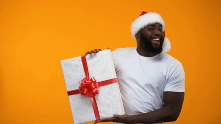 xマス : Santa man holding gift box and winking, holidays discounts, time to buy presents 動画素材
