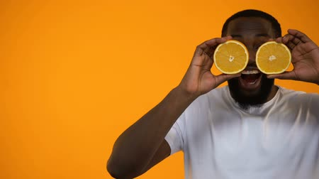 laranjas : Funny African-American man clothing eyes with half of oranges, healthy lifestyle Vídeos