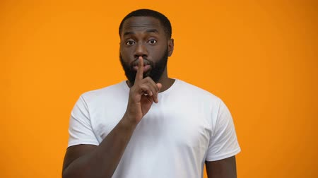 consulta : African-American man showing silence gesture, keeping secret, yellow background