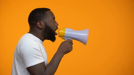 political speech : African-American man using megaphone for protest, calling to action, side view