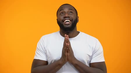 umma : Happy African-American man holding hands for pray and looking up, blessing god Stok Video