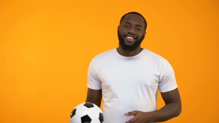 league : Attractive Afro-American man playing with soccer ball and showing thumbs up sign Stock Footage