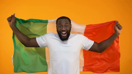 favori : Excited black sport fan waving Italian flag, cheering for victory, patriotism Stok Video