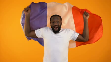 favori : African-American man waving French flag, football fan supporting national team Stok Video