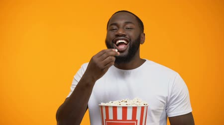 blockbuster : Cheerful Afro-American man eating popcorn and laughing out loud, comedy show