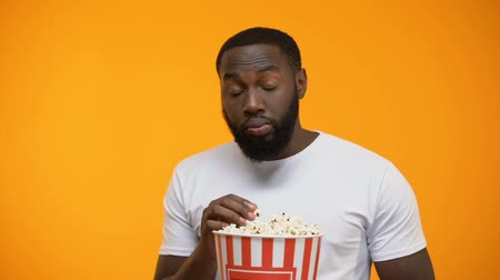 érdekes : African-American man with popcorn attentively watching interesting TV program