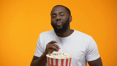 serial : Afro-American man eating popcorn and watching interesting serial, close-up