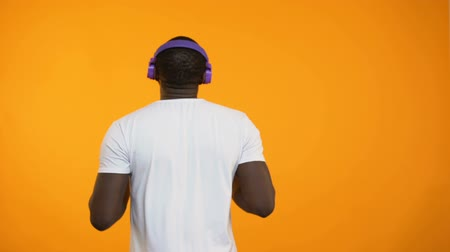 favori : Afro-American man in headphones dancing actively performing winner moves closeup Stok Video
