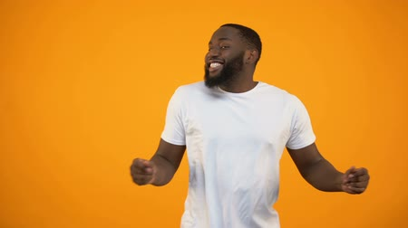 movimentar se : Afro-American man dancing against yellow background, feeling rhythm of music