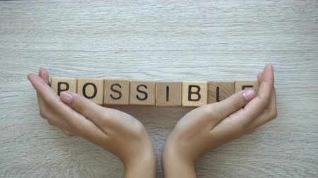 ösztönző : Possible, hands pushing word on wooden cubes, possibilities motivation and goals