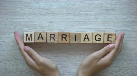 casar : Marriage, hands pushing word on wooden cubes, family wife husband and children