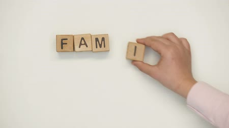 together trust : Family word made by mothers and childs hands on wooden cubes, holding heart Stock Footage