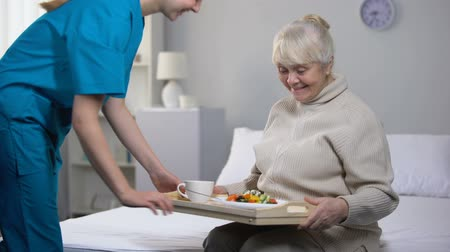 служить : Medical worker serving dinner to happy old lady, good hospital services, care