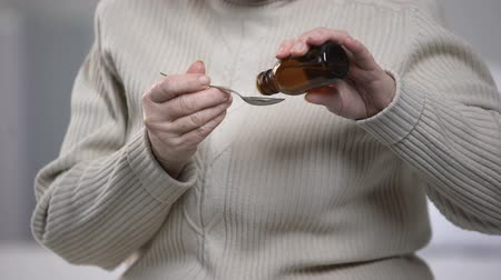 sirup : Old lady pouring cough syrup in spoon with trembling hands, health treatment Dostupné videozáznamy