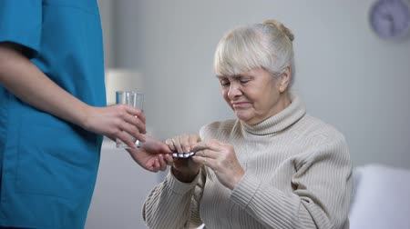 segítség : Nurse giving painkillers elderly woman suffering from headache, taking care