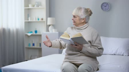blindness : Elderly woman holding book asking nurse for eyeglasses, vision problems, health Stock Footage