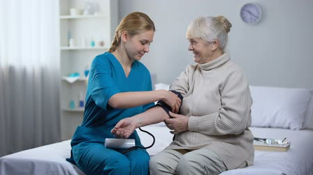 examinar : Cardiologist measuring old female patient blood pressure, professional medicare