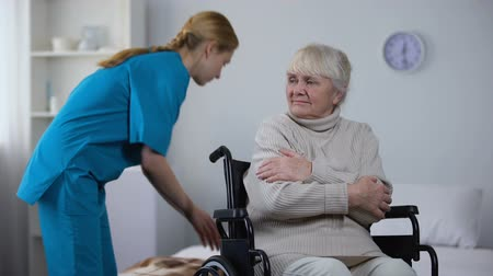 paraplegic : Kind nurse covering with blanket handicapped old woman shivering from cold