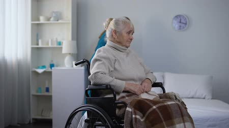sanitize : Sad woman in wheelchair watching hospital janitor cleaning room, medical center