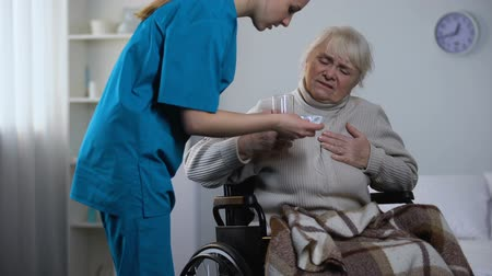 подопечный : Old lady in wheelchair feeling heart pain, asking nurse for pills, hospital care