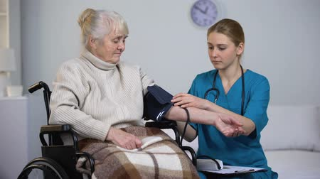 sphygmomanometer : Doctor measuring blood pressure of old patient, writing examinations results