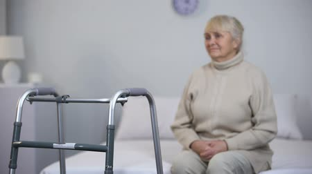 подопечный : Upset old woman sitting near walking frame, disability after joint surgery