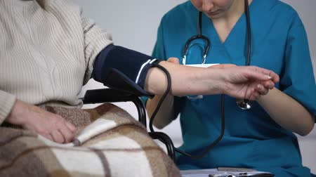 sphygmomanometer : Therapist measuring blood pressure of old lady, writing examinations results