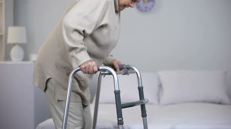chirurgia : Old woman slowly walking with frame, rehabilitation after trauma, joint surgery Wideo