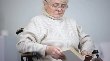 lonely : Sad disabled woman in eyeglasses reading book in nursing home, depression