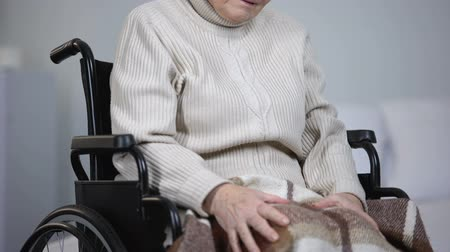 osteoarthritis : Elderly woman in wheelchair massaging painful knee joints, health problems Stock Footage