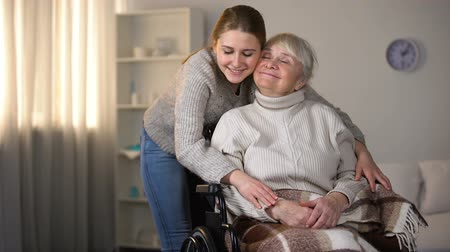 assistência médica : Granddaughter hugging smiling old woman in wheelchair, family love and care