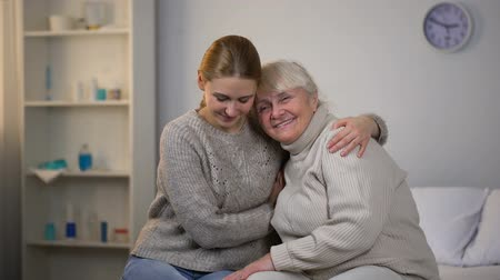 caregiver : Caring girl hugging disabled grandmother, supportive relationships in family Stock Footage