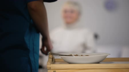 caregiver : Young nurse serving dinner to old handicapped lady, taking care about patient