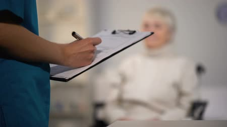 examinar : Therapist making notes in medical records and examining elderly lady, hospital Stock Footage
