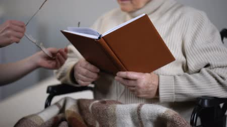 peça : Woman giving eyeglasses to old lady in wheelchair reading book, hospital care