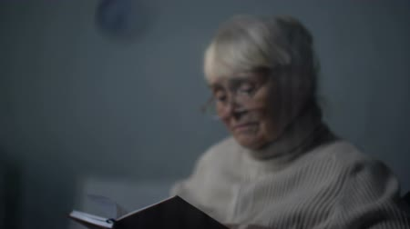 bilge : Upset elderly lady reading book in dark room on rainy day, loneliness in old age