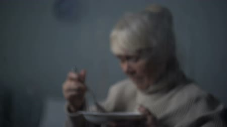 hemşirelik : Old woman eating unappetizing dinner, sitting in dark room on rainy day, clinic Stok Video