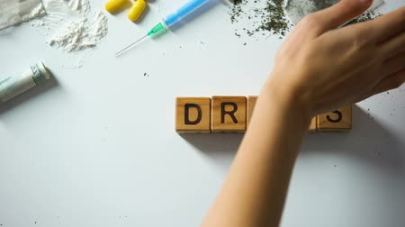 denied : No drugs words made of wooden cubes, hand cleaning table from narcotics, concept