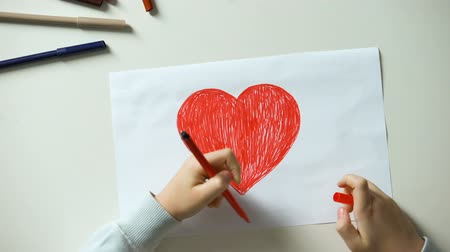 verdadeiro : Child painting red heart, putting love word made of wooden cubes on sides Stock Footage