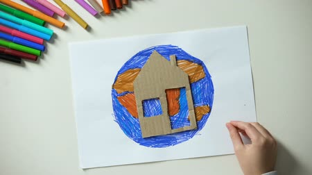 salva vidas : Kid putting paper house and heart sign near Earth painting, world our home