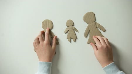 gerek : Child putting paper family and heart on white background, orphan needs home Stok Video