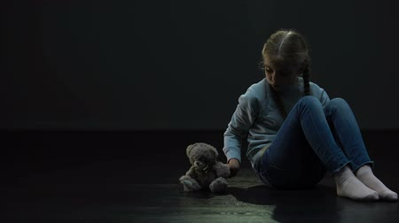 hajléktalan : Little girl sitting alone in dark room and hugging teddy bear, lack of friends