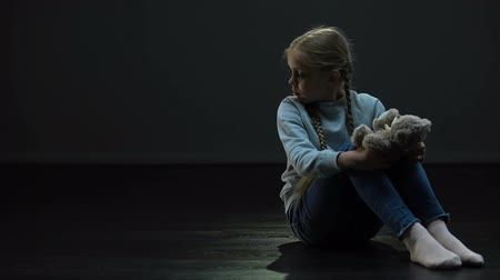 verwarring : Little girl with teddy bear sitting alone in dark room, looking around, orphan Stockvideo
