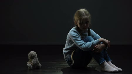 irreal : Depressed little girl feeling lonely, hugging teddy bear, sitting in dark room Stock Footage
