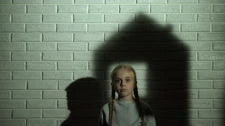 evsiz : House shadow on wall behind little girl, orphan child needs home and family