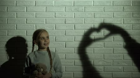 umma : Girl looking at heart shadow on wall and hugging teddy bear, hope and kindness