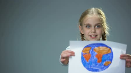 salva vidas : Smiling little child showing Earth picture into camera, global peace concept