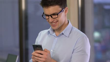 hírnök : Smiling businessman scrolling smartphone, reading message, mobile communication